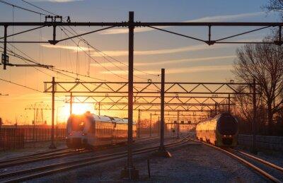 Obraz Pociągi pozostawiając stację podczas wschodu słońca zimą.