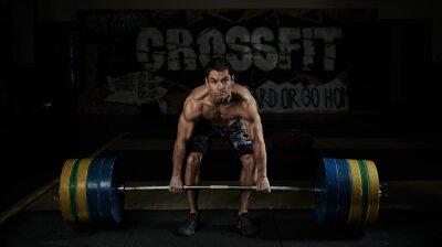 Obraz Podnoszenie ciężarów. Sport. Wytrzymałość. Muskularny półnagi zawodnik podnoszenia ciężkich sztangą na siłowni.