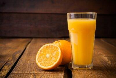 Obraz Pomarańczowe owoce i szkła soku na brązowym tle drewnianych