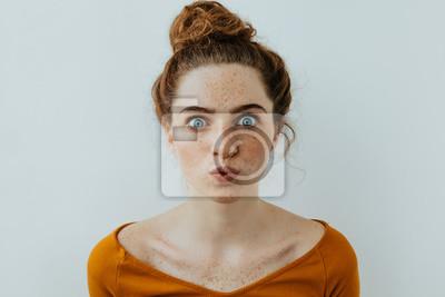 Obraz Portret kobiety. Styl. Piękna błękitnooka dziewczyna z piegami bieli wargi przy kamerą, na białym tle