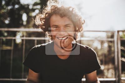 Obraz Portret zbliżenie zewnątrz przystojny piegowaty uśmiechnięty mężczyzna z kręconymi włosami, pozowanie do reklamy społecznej, na ulicy miasta na zachód słońca światło słoneczne z miejsca na kopię dla i