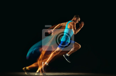 Obraz Professional male runner training isolated on black studio background in mixed light. Man in sportsuit practicing in run or jogging. Healthy lifestyle, sport, workout, motion and action concept.