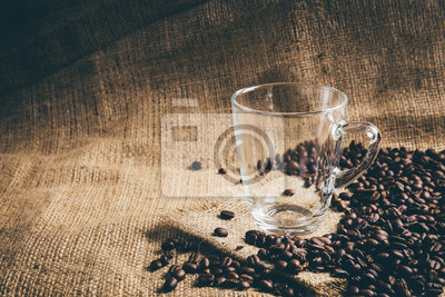 Pusty szklany kubek z ziaren kawy na tradycyjnym workiem tekstylnym. Vintage retusz.