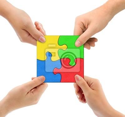 Ręce i puzzle drużyny