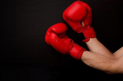 Obraz Ręka w czerwonym rękawice bokserskie w rogu ramki na czarnym tle, pusta przestrzeń