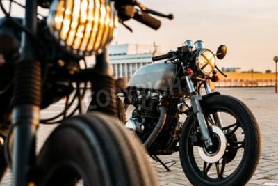 Obraz Rocznik motocykla niestandardowych cafe racer motocykl z lamp światła włączone. Jeden z grillem reflektorów innej taśmy z krzyżem nad optyką na pustym parkingu na dachu partii podczas zachodu słońca.