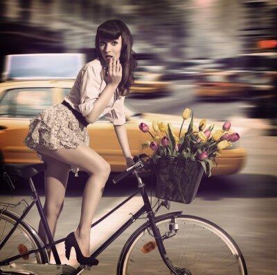 Obraz rocznika kobieta na rowerze na ulicy miasta z taksówką