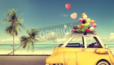 Obraz Rocznika żółty samochód z kierowym kolorowym balonem na plażowym niebieskim niebie - pojęcie miłość w lecie i ślubie. Podróż poślubna