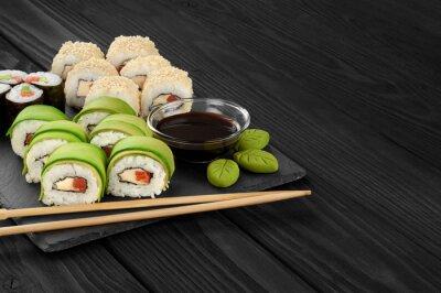 Obraz Rolki sushi z awokado, łososia i sezamem na tacy łupków.