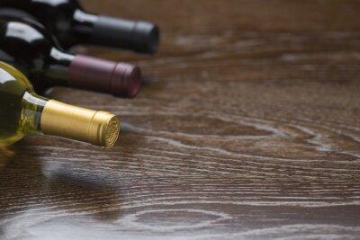 Obraz Różnych butelek wina na odblaskowej powierzchni drewna Streszczenie