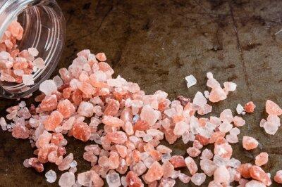 Obraz Rozproszone Himalayan różowe kryształy soli z szklanej butelce na zardzewiały metal tle