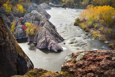 rzeka w długim czasie ekspozycji i brzegi rzeki w jesiennych barwach ze skałami