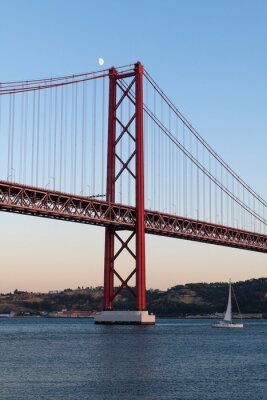 Sailing boat in the Tagus River passing by the 25 of April Bridge (Ponte 25 de Abril), in the city of Lisbon, Portugal; Concept for travel in Portugal