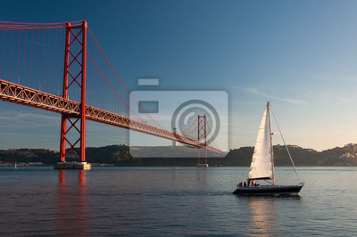 Sailing boat passing by the 25 of April Bridge (Ponte 25 de Abril) over the Tagus River in the city of Lisbon, Portugal; Concept for travel in Portugal