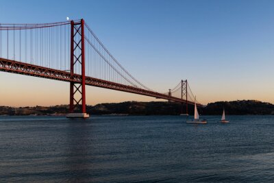 Sailing boats in the Tagus River passing by the 25 of April Bridge (Ponte 25 de Abril), in the city of Lisbon, Portugal; Concept for travel in Portugal