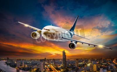 Obraz Samolot dla transportu lata nad nocy sceny miastem na pięknym zmierzchu tle