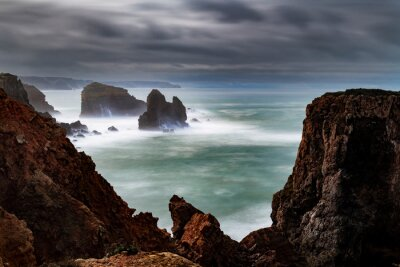 Scenic view of the coastline along Carrapateira with the rock formations and waves crashing during a storm, in Algarve, Portugal