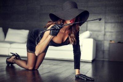 Obraz Sexy kobieta w kapelusz i bicz klęczy na podłodze w pomieszczeniach