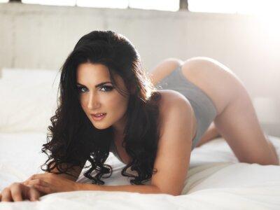 Obraz sexy modelu na jasno oświetlonym łóżku w erotycznej pozie