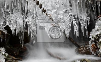 Siklawa z lodowymi kryształami tworzy na zimy górskim zatoczce.