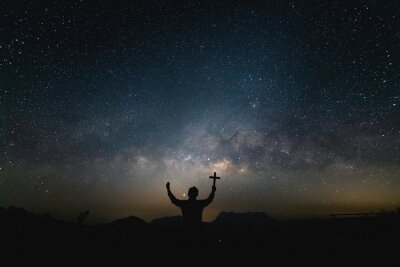 Obraz Silhouette Human praying and holding christian cross for worshipping God at Night landscape with colorful Milky Way.