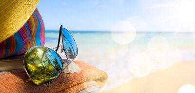 Obraz Słomkowy kapelusz, torba i okulary na tropikalnej plaży
