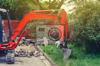 Obraz Small excavator on sidewalk near lawn. Repair in city, urban