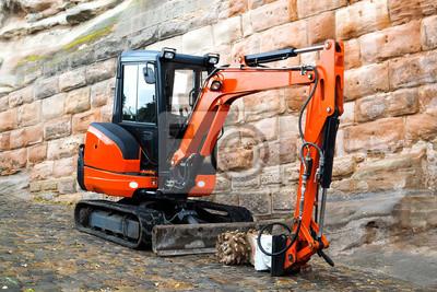 Obraz Small machine res excavator on sidewalk during repair works on street in urban environment