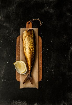 Obraz Smoked mackerel and lemon slices on black from above