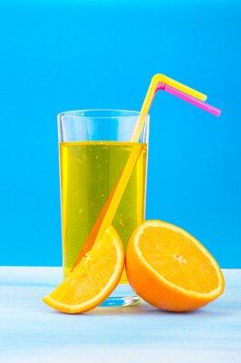 Obraz Sok pomarańczowy w szklance z kolorowych słomek i plastry pomarańczy na niebieskim tle