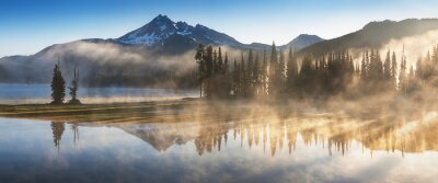 Obraz South Sister and Broken Top reflect over the calm waters of Sparks Lake at sunrise in the Cascades Range in Central Oregon, USA in an early morning light. Morning mist rises from lake into trees.