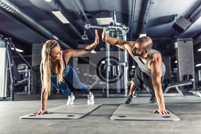 Obraz Sport couple doing plank exercise workout in fitness centrum. Man and woman practicing plank in the gym