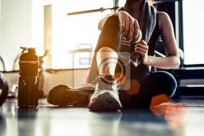 Obraz Sport kobieta siedzi i odpoczynku po treningu lub ćwiczeń w siłowni fitness z białka wstrząsnąć lub wody pitnej na podłodze. Relaks koncepcja. Trening siłowy i temat budowy ciała. Ciepły i fajny ton