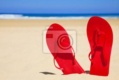 Stały czerwony sandały na pusty plaży