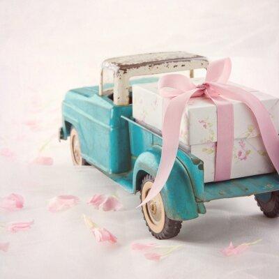 Obraz Stare zabytkowe zabawki ciężarówki przewożących pudełko z różową wstążką