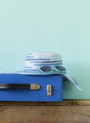 Obraz staroświecki niebieski walizki na podróż i na plaży kapelusz