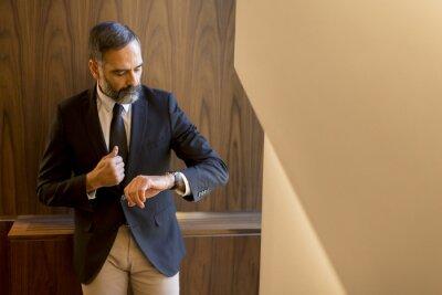 Obraz Senior businessman looking on the watch