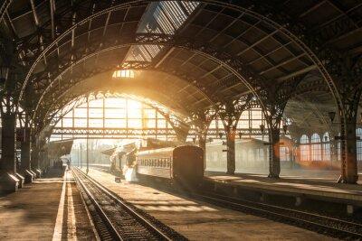 Obraz Stary dworzec kolejowy z pociągiem i lokomotywą na peronie czekającym na odjazd. Wieczorne promienie słońca w łukach dymu.