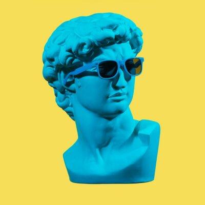 Obraz Statue. Earphone. Isolated. Gypsum statue of David's head. Man. Creative. Plaster statue of David's head in blue sunglasses. Minimal concept art.