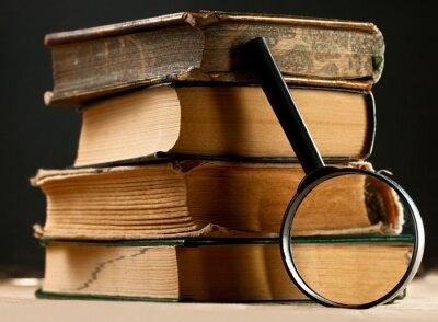 Obraz Stos starych książek z lupą