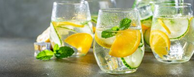 Obraz Summer healthy lemonade, cocktails of citrus infused water or mojitos, with lime lemon orange, ice and mint, diet detox beverages, in glasses on gray background. Banner