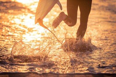 Obraz Surfer pracuje w wodzie z jego zarządu