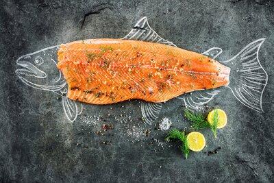 Obraz surowe ryby łososia stek z dodatkami takimi jak cytryny, pieprz, sól morska i koperkiem na czarnej tablicy, naszkicowany obraz kredą łososia stek z ryby
