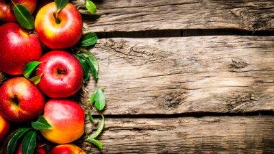 Obraz Świeże czerwonych jabłek z zielonymi liśćmi na drewnianym stole.
