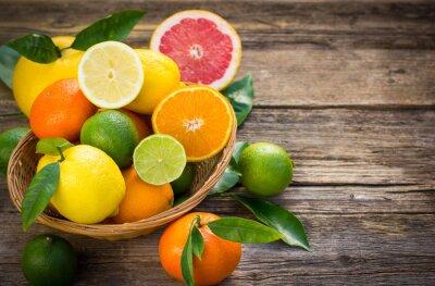 Obraz Świeże i soczyste owoce cytrusowe w koszyku na tamtejsze tabeli
