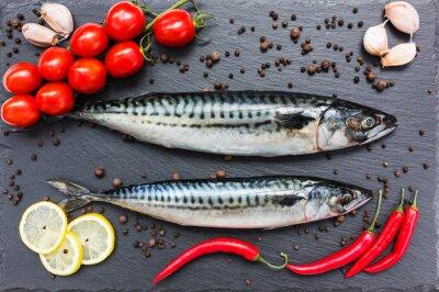 Obraz Świeże ryby makrele, papryka chili, cytryny, pomidory, czosnek cięcia na pokładzie łupków. Widok z góry