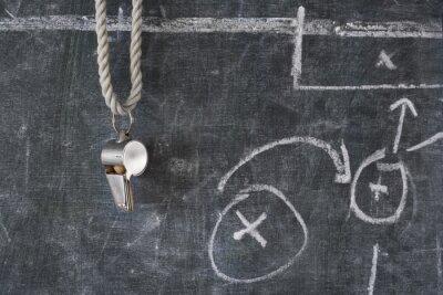 Obraz świst piłki nożnej lub sędziego piłki nożnej na tablicy z schematem taktycznym