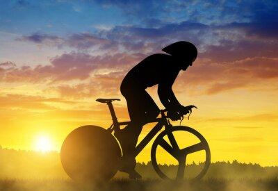 Obraz Sylwetka rowerzysty na rowerze wyścigowym drogi o zachodzie słońca.