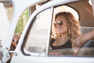 Obraz Szczęśliwy, beztroski kobieta cieszyć retro samochód, gorący letni dzień.