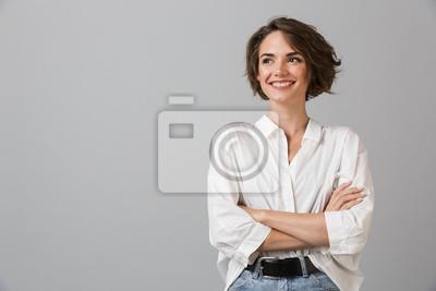 Obraz Szczęśliwy młody biznes kobieta pozowanie na białym tle na szarym tle ściany.